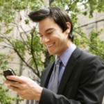 Businessman smiling at cell phone message.